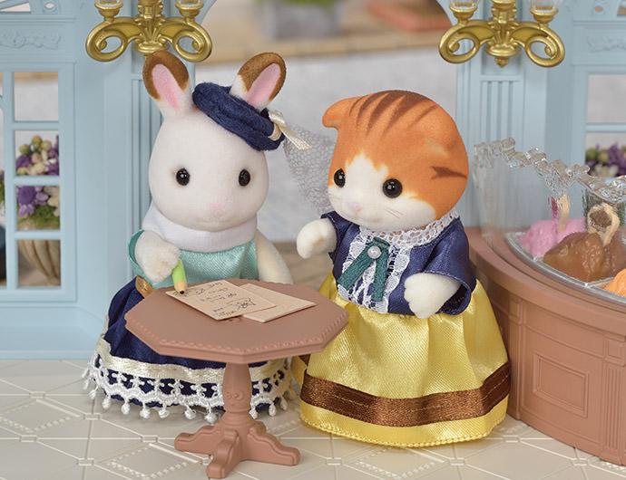 """An einem anderen Tag kam die Ahornkatzen Mutter Giulia und fragte Stella nach einem Kleid für ihre Tochter Emily.            Stella Löffel fragte Giulia Knickohr alle möglichen Fragen. """"When is Millie's birthday?"""" she asked. """"And what's her favourite flower?""""  So wusste Stella, wie man die perfekten Kleider für jeden entwerfen konnte. Sie fragt immer nach den Lieblingsblumen und den Edelsteinen die ihre Kunden am liebsten mögen und nutzt diese Informationen für ihre Kleider."""