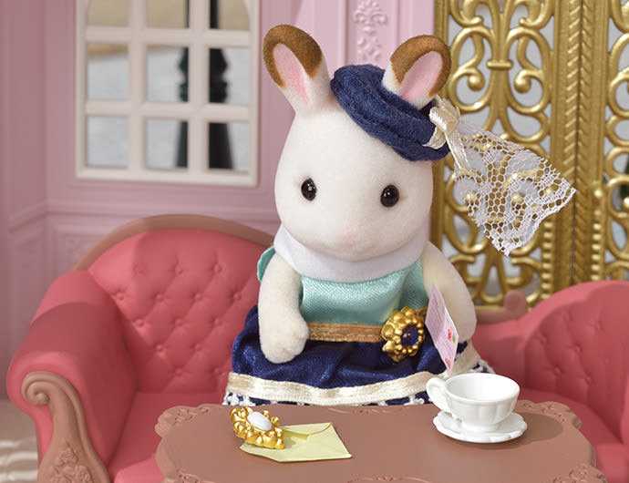 """Un jour Stella reçu une lettre de sa petite sœur Freya, la fille Lapin Chocolat.  La lettre disait, """"Maman m'a acheté une magnifique broche ! Pourrais-tu, s'il te plait, me confectionner une robe que je porterai avec ?""""  Stella trouva la broche dans l'enveloppe. Elle imagina alors à quel point Freya devait être heureuse d'avoir reçu un aussi joli cadeau et ne pu s'empêcher de sourire."""
